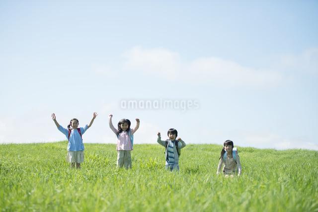 草原で両手を挙げる小学生の写真素材 [FYI04550999]