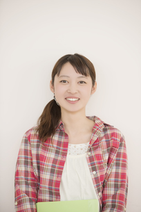 勉強道具を持ち微笑む大学生の写真素材 [FYI04551028]