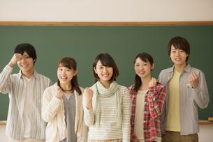 黒板の前でガッツポーズをする大学生の写真素材 [FYI04551051]