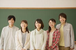 黒板の前で微笑む大学生の写真素材 [FYI04551053]