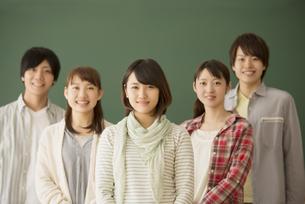 黒板の前で微笑む大学生の写真素材 [FYI04551055]