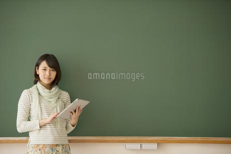 黒板の前で微笑む大学生の写真素材 [FYI04551060]