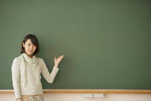 黒板の前で微笑む大学生の写真素材 [FYI04551061]
