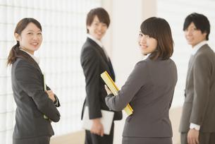 オフィスの廊下で振り返るビジネスウーマンとビジネスマンの写真素材 [FYI04551123]
