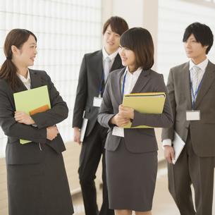 オフィスの廊下を歩くビジネスウーマンとビジネスマンの写真素材 [FYI04551125]
