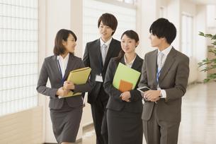 オフィスの廊下を歩くビジネスウーマンとビジネスマンの写真素材 [FYI04551131]