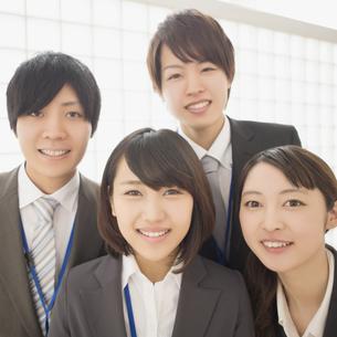 オフィスで微笑むビジネスウーマンとビジネスマンの写真素材 [FYI04551196]