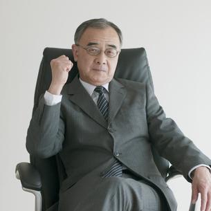 椅子に座りガッツポーズをするビジネスマンの写真素材 [FYI04551253]