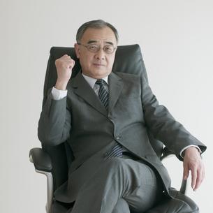 椅子に座りガッツポーズをするビジネスマンの写真素材 [FYI04551254]