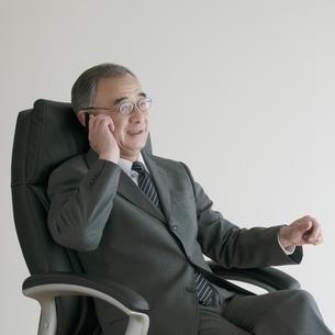 椅子に座り電話をするビジネスマンの写真素材 [FYI04551257]