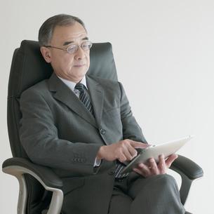 椅子に座りタブレットPCを操作するビジネスマンの写真素材 [FYI04551262]