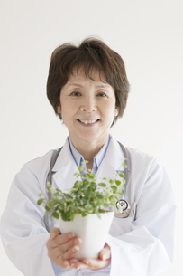 植物を持ち微笑む女医の写真素材 [FYI04551278]