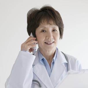 カルテを持ち電話をする女医の写真素材 [FYI04551280]