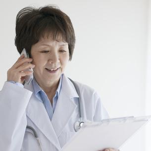 カルテを見ながら電話をする女医の写真素材 [FYI04551284]