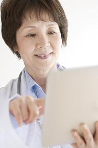 タブレットPCを操作する女医の写真素材 [FYI04551312]
