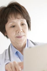 タブレットPCを操作する女医の写真素材 [FYI04551314]