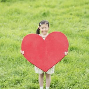 草原でハートを持ち微笑む女の子の写真素材 [FYI04551360]