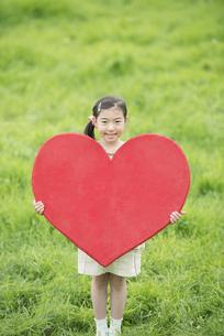 草原でハートを持ち微笑む女の子の写真素材 [FYI04551362]