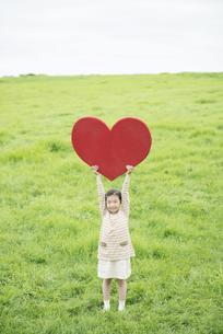草原でハートを持ち微笑む女の子の写真素材 [FYI04551364]