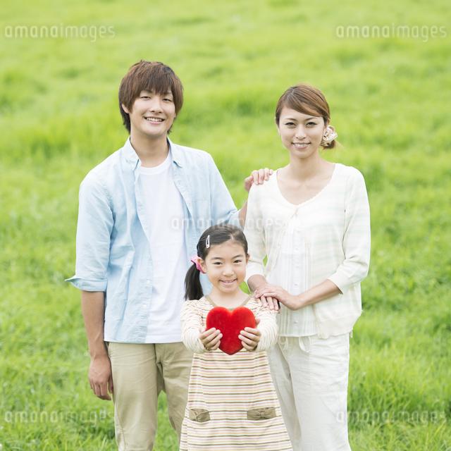 草原でハートを持ち微笑む親子の写真素材 [FYI04551368]