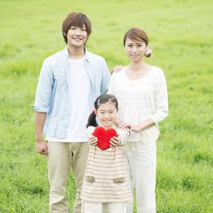 草原でハートを持ち微笑む親子の写真素材 [FYI04551370]