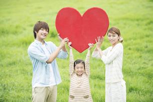 草原でハートを持ち微笑む親子の写真素材 [FYI04551371]