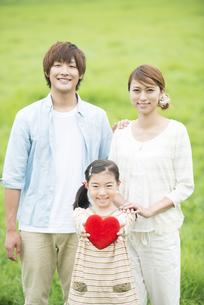 草原でハートを持ち微笑む親子の写真素材 [FYI04551372]