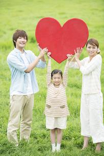 草原でハートを持ち微笑む親子の写真素材 [FYI04551374]