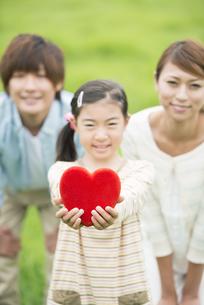 草原でハートを持ち微笑む親子の写真素材 [FYI04551375]