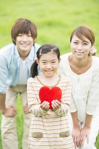 草原でハートを持ち微笑む親子の写真素材 [FYI04551376]