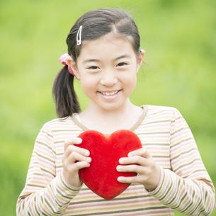 草原でハートを持ち微笑む女の子の写真素材 [FYI04551377]