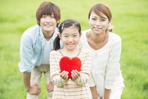 草原でハートを持ち微笑む親子の写真素材 [FYI04551378]
