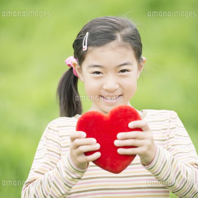 草原でハートを持ち微笑む女の子の写真素材 [FYI04551379]