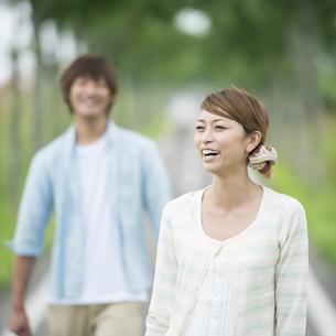 一本道で微笑むカップルの写真素材 [FYI04551387]