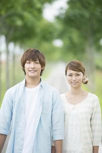 一本道で微笑むカップルの写真素材 [FYI04551388]