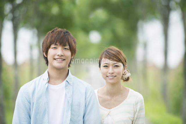 一本道で微笑むカップルの写真素材 [FYI04551389]