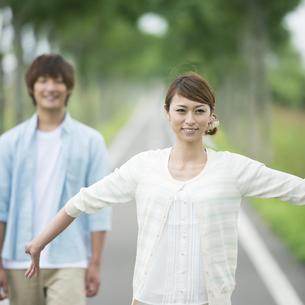 一本道で微笑むカップルの写真素材 [FYI04551391]