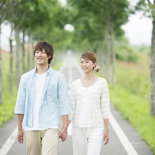 一本道で手をつなぐカップルの写真素材 [FYI04551392]