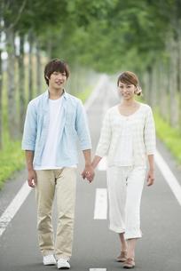 一本道で手をつなぐカップルの写真素材 [FYI04551393]