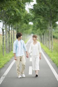 一本道で手をつなぐカップルの写真素材 [FYI04551395]