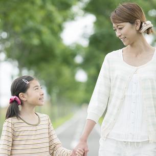 一本道で手をつなぐ親子の写真素材 [FYI04551406]