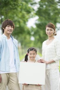 一本道でメッセージボードを持つ親子の写真素材 [FYI04551409]
