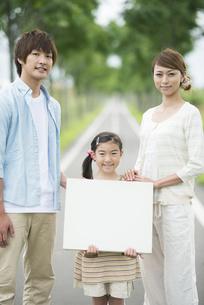 一本道でメッセージボードを持つ親子の写真素材 [FYI04551410]