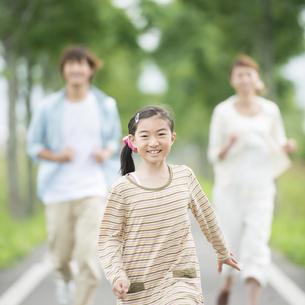 一本道を走る親子の写真素材 [FYI04551412]