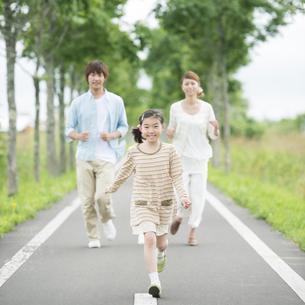 一本道を走る親子の写真素材 [FYI04551414]