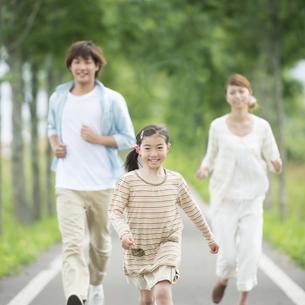一本道を走る親子の写真素材 [FYI04551416]