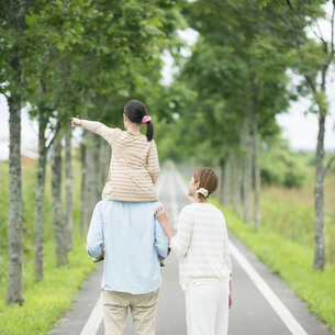 一本道で肩車をする親子の後姿の写真素材 [FYI04551422]