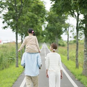 一本道で肩車をする親子の後姿の写真素材 [FYI04551424]