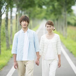 一本道で手をつなぐカップルの写真素材 [FYI04551429]