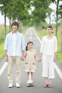 一本道で手をつなぐ親子の写真素材 [FYI04551438]